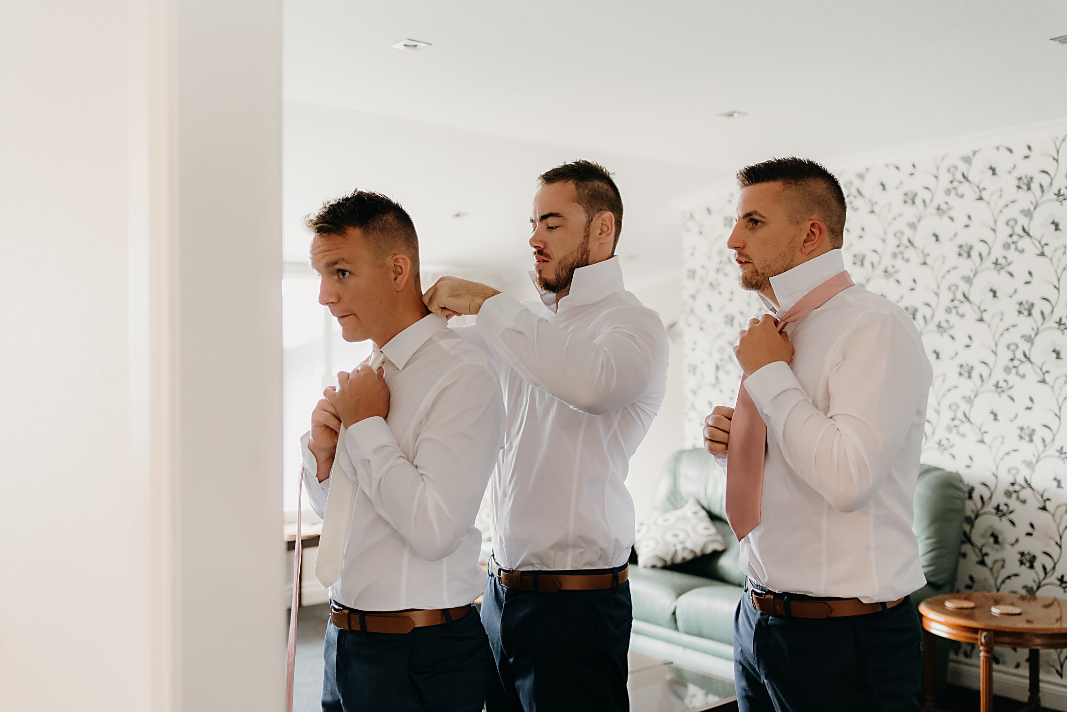 groomsmen tying his tie